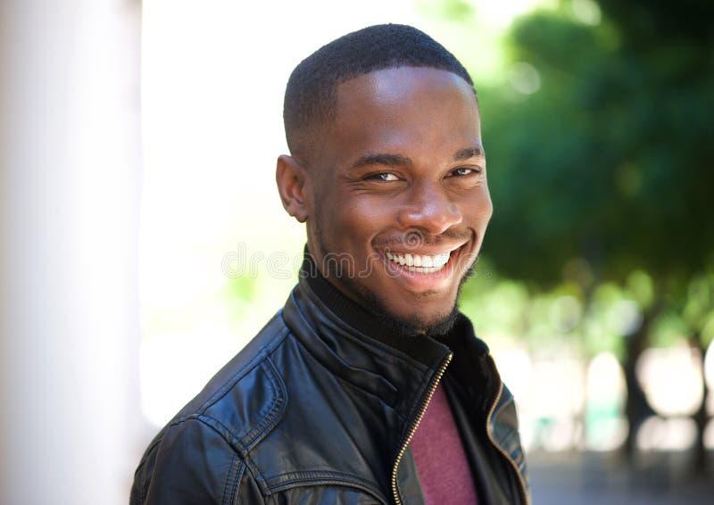 Jeune homme gai d'afro-américain souriant dehors images libres de droits