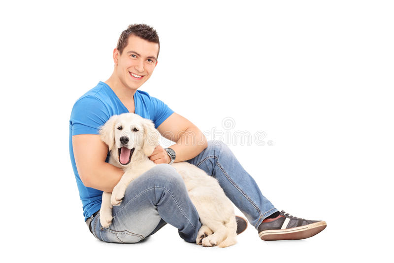 Jeune homme gai posant avec un petit chiot mignon photos libres de droits