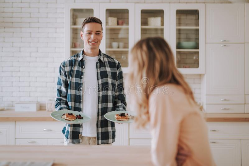 Jeune homme gai tenant des cr?pes des plats et du sourire photo stock