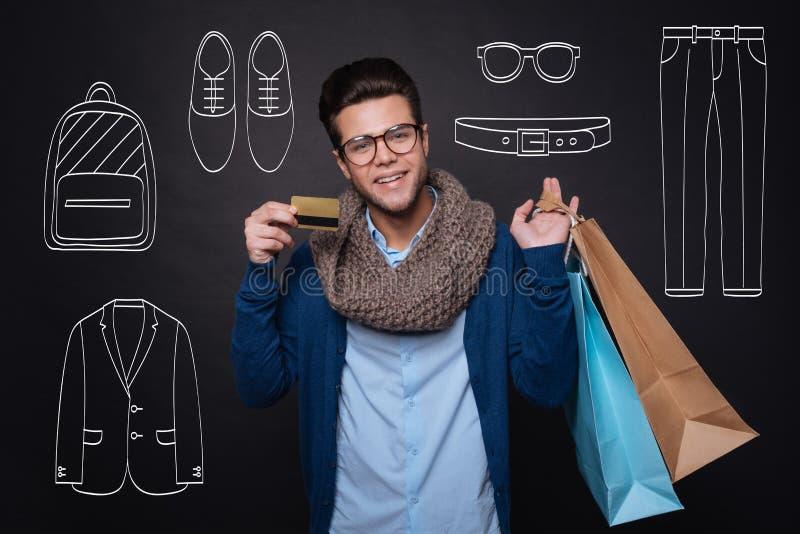 Jeune homme gai tenant des paniers et montrant la carte de remise images libres de droits