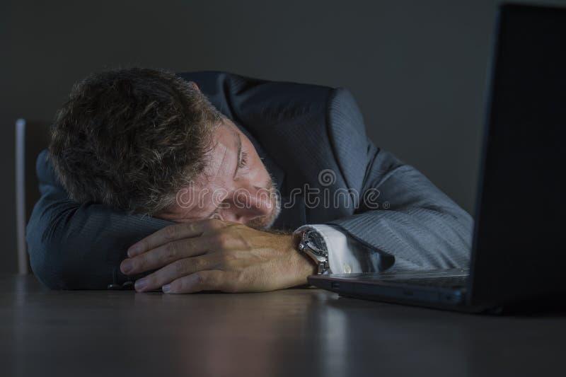 Jeune homme gaspillé et fatigué attirant d'entrepreneur dormant prenant le petit somme de fin de nuit au bureau d'ordinateur port photos libres de droits