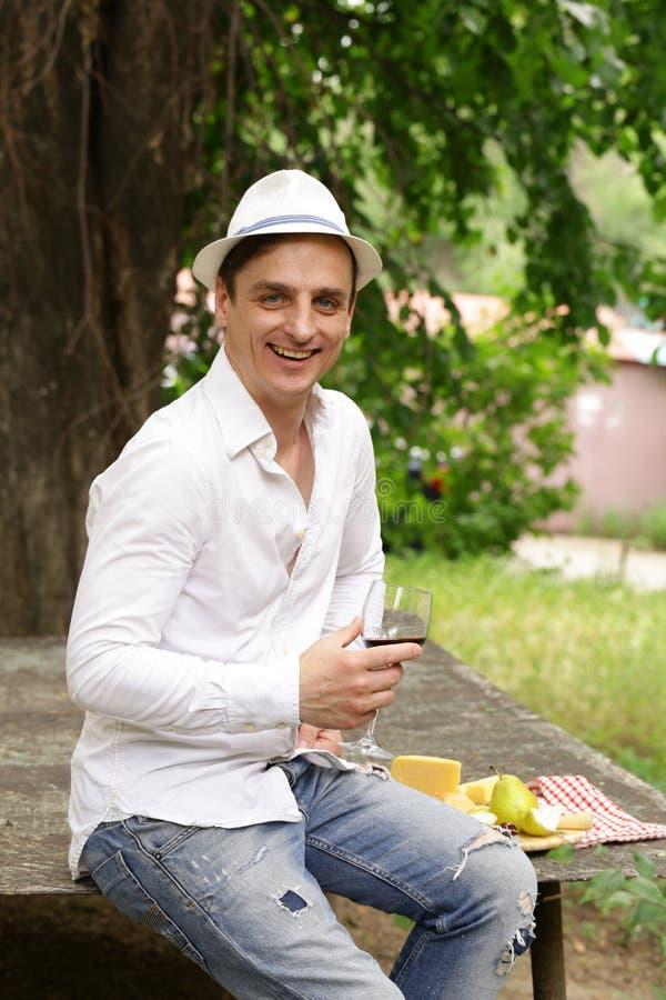 Jeune homme goûtant le vin rouge avec le panneau de fromage images libres de droits