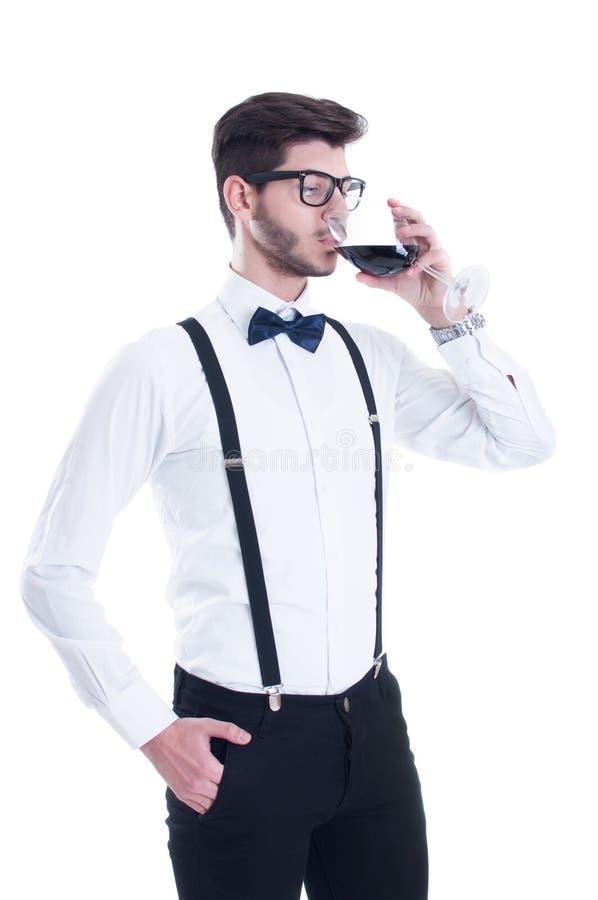 Jeune homme goûtant le vin rouge D'isolement sur le fond blanc photos stock