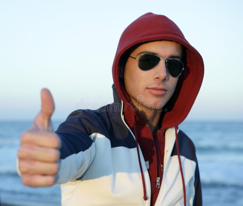 Jeune homme grunge avec le capot à la plage photos stock
