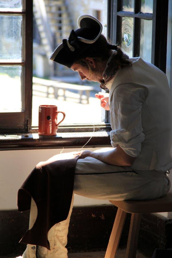 Jeune homme habillé comme tailleur, travaillant dans la lumière de la fenêtre, fort Ticonderoga, 2014 image stock