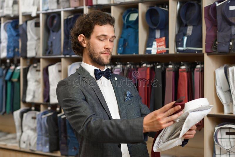 Jeune homme hansome de brune choisissant l'article dans la boutique photographie stock