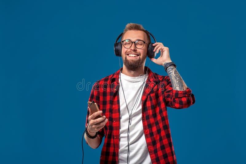 Jeune homme heureux écoutant la musique avec des écouteurs Type de sourire beau dans la chemise à carreaux avec la danse fermée d photographie stock