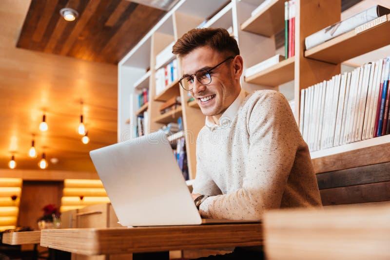 Jeune homme heureux attirant à l'aide de l'ordinateur portable photos libres de droits