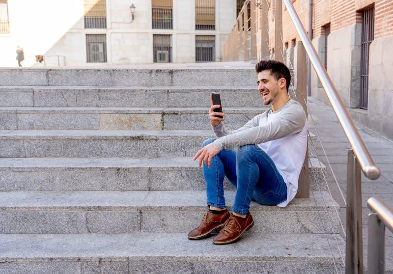 Jeune homme heureux attirant de hippie parlant au téléphone intelligent dans l'EUR image stock