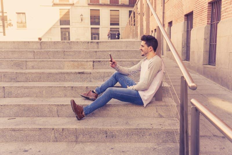 Jeune homme heureux attirant de hippie parlant au téléphone intelligent dans l'EUR photo stock