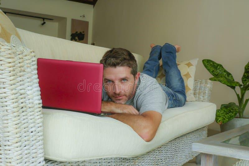 Jeune homme heureux attirant et bel se trouvant à la maison divan de sofa fonctionnant avec le netbook d'ordinateur portable déco photographie stock