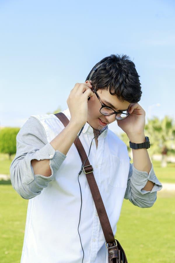 Jeune homme heureux avec des écouteurs et le sourire, dehors photographie stock libre de droits
