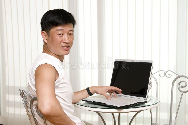 Jeune homme heureux avec l'ordinateur portatif image stock