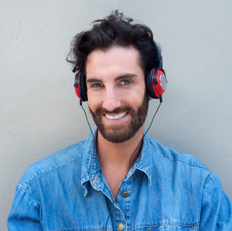 Jeune homme heureux avec la barbe écoutant la musique avec des écouteurs images libres de droits