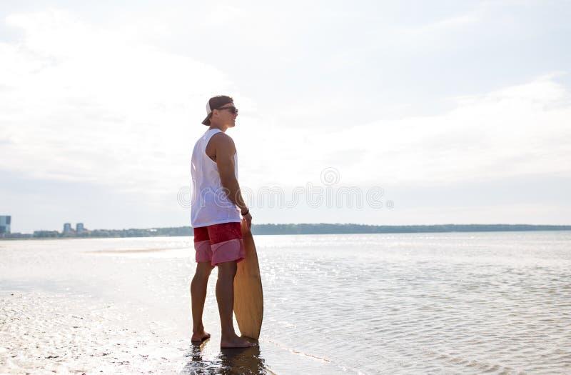 Jeune homme heureux avec le skimboard sur la plage d'été image stock