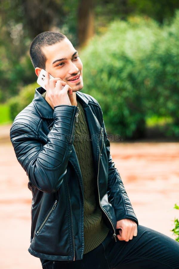 Jeune homme heureux avec le smartphone Parler au téléphone photographie stock libre de droits