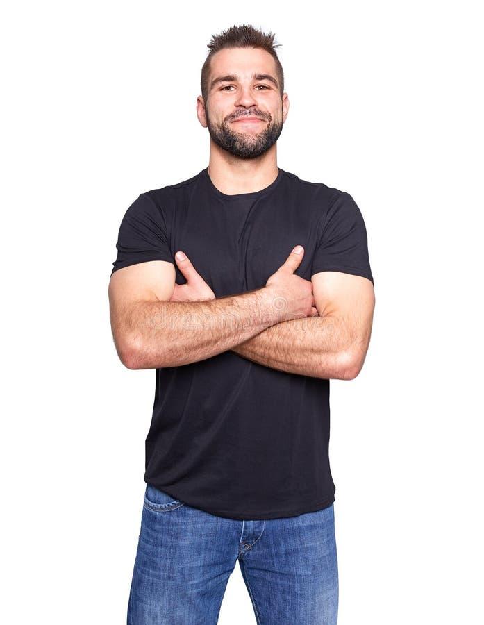 Jeune homme heureux avec les mains croisées dans un T-shirt noir photographie stock libre de droits