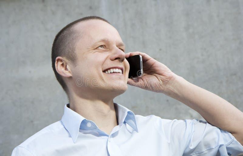 Jeune homme heureux d'affaires parlant au téléphone. image stock