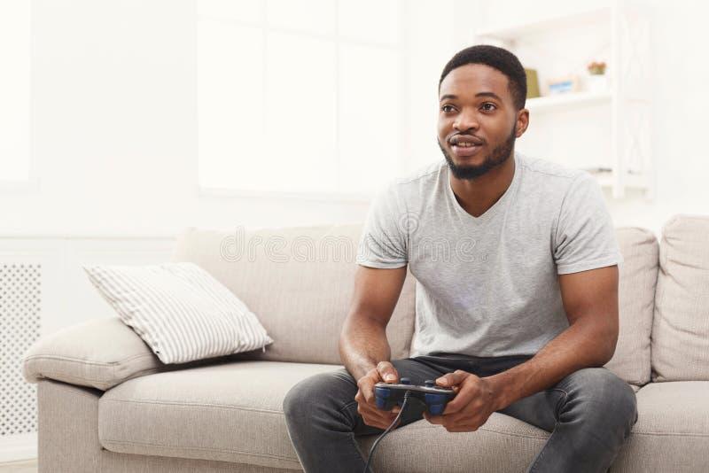 Jeune homme heureux d'afro-américain à la maison jouant des jeux vidéo photographie stock