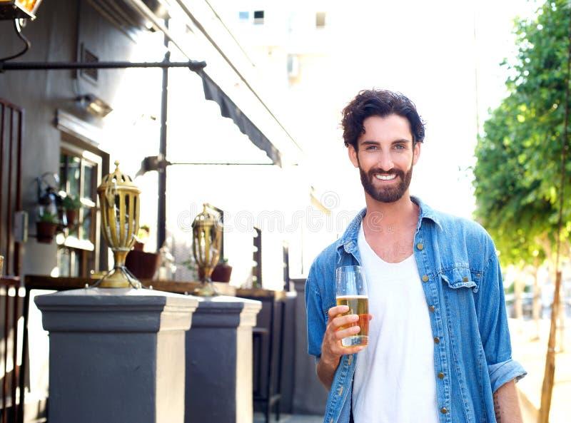 Jeune homme heureux dans la chemise bleue tenant le verre de bière dehors images stock