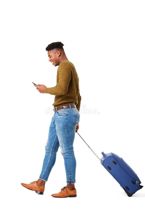 Jeune homme heureux de voyage d'afro-américain marchant avec le téléphone portable et la valise sur le fond blanc d'isolement photo libre de droits