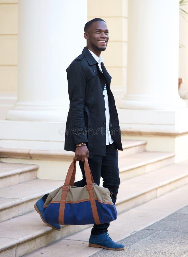 Jeune homme heureux descendant des étapes d'hôtel avec le sac photo libre de droits
