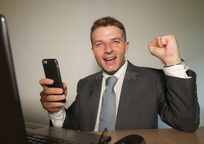 Jeune homme heureux et attirant d'affaires travaillant avec le téléphone portable au bureau d'ordinateur de bureau célébrant fair photographie stock libre de droits