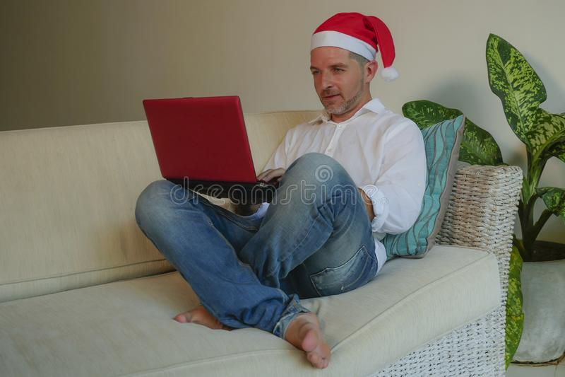 Jeune homme heureux et attirant dans le chapeau de Santa Klaus utilisant la carte de crédit et l'ordinateur portable pour acheter photos stock