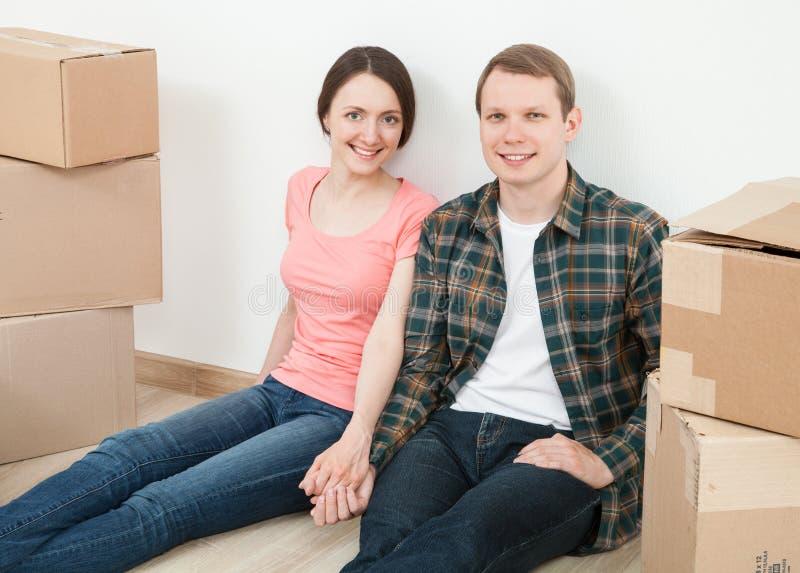 Jeune homme heureux et femme s'asseyant près des boîtes en carton images libres de droits