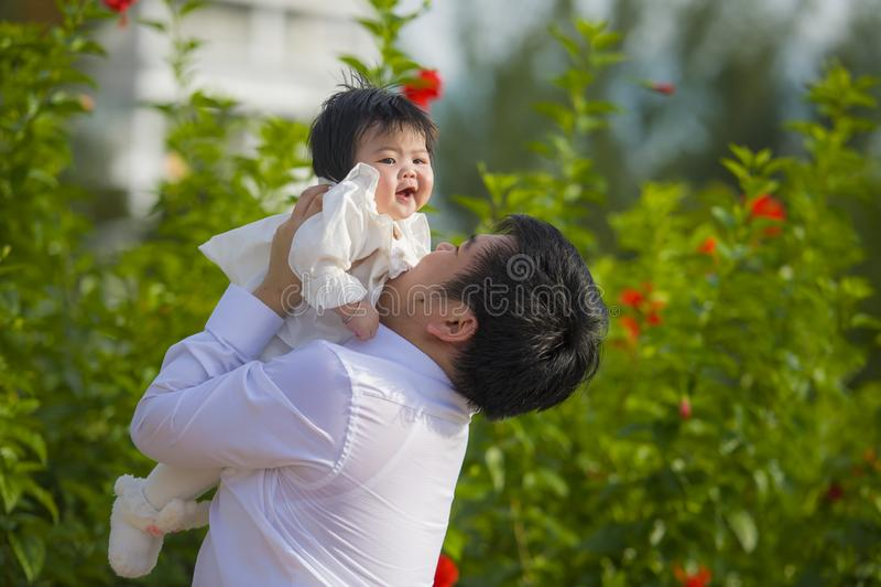 Jeune homme heureux et fier comme père du petit bébé doux tenant sa fille devant le jardin de fleurs à la station de vacances de  photographie stock libre de droits