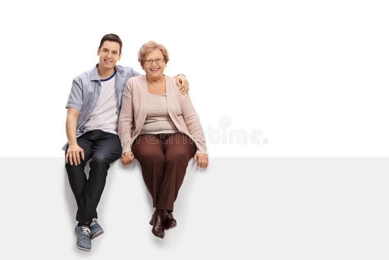 Jeune homme heureux et une femme mûre s'asseyant ensemble sur un panneau image libre de droits