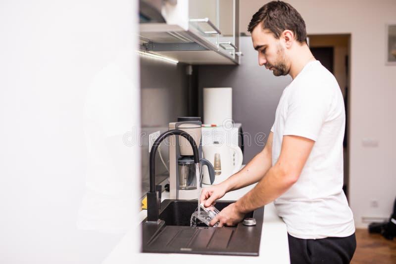 Jeune homme heureux faisant la vaisselle souriant travail domestique faisant appréciant sûr et décontracté dans l'amusement et le photos libres de droits