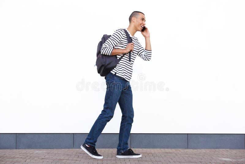 Jeune homme heureux marchant avec le sac et parlant au téléphone portable contre le mur blanc image stock