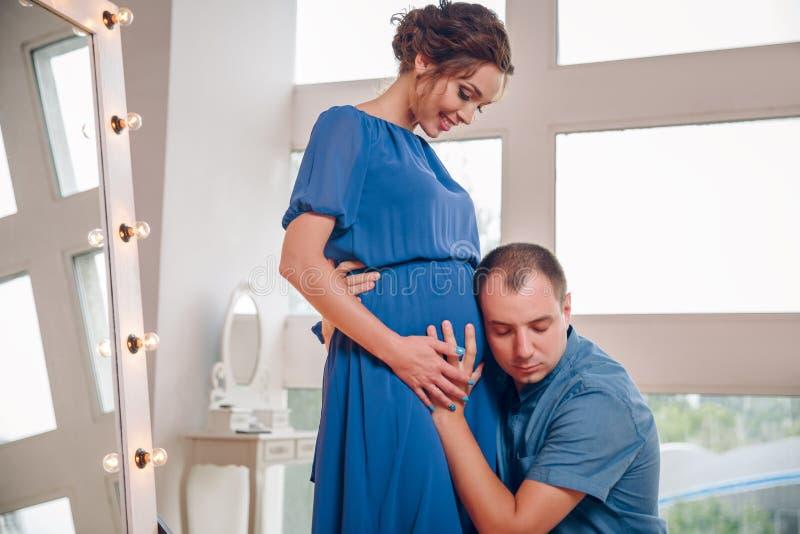 Jeune homme heureux mettant l'oreille au ventre de femme enceinte écoutant le bébé se déplaçant à l'intérieur, mari curieux affec image libre de droits