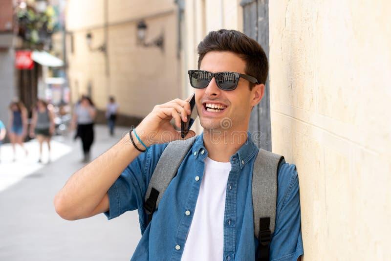 Jeune homme heureux moderne beau parlant à son téléphone intelligent dehors dans la ville photographie stock libre de droits