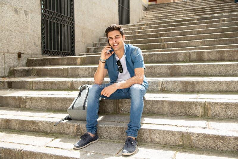 Jeune homme heureux moderne beau parlant à son téléphone intelligent dehors dans la ville images stock