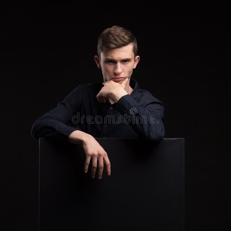 Jeune homme heureux montrant la présentation, se dirigeant sur la plaquette au-dessus de g photo stock