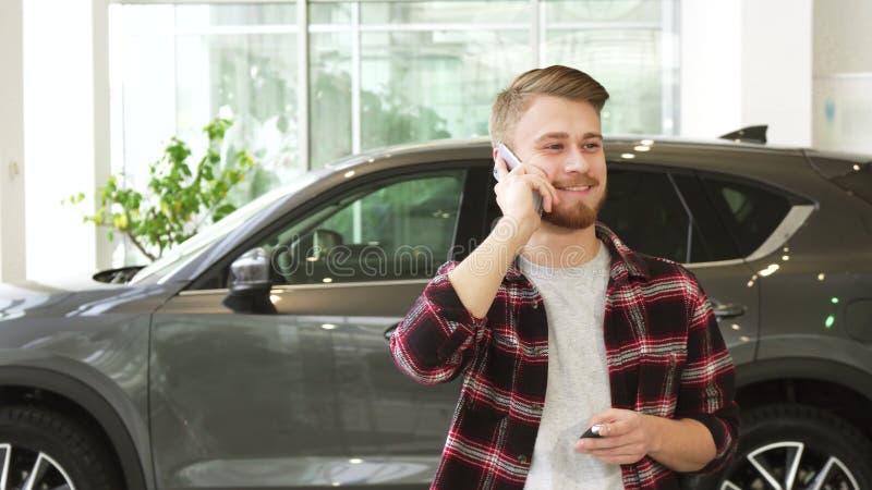 Jeune homme heureux parlant au téléphone après l'achat d'une nouvelle voiture au dealrrship photographie stock