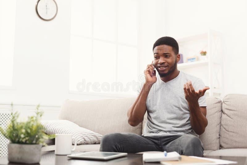 Jeune homme heureux parlant sur le mobile à la maison photographie stock