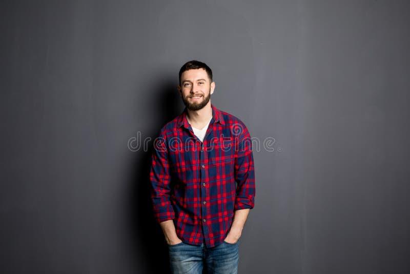 Jeune homme heureux Portrait de jeune homme beau dans la chemise occasionnelle avec des mains dans des poches et le sourire photos libres de droits