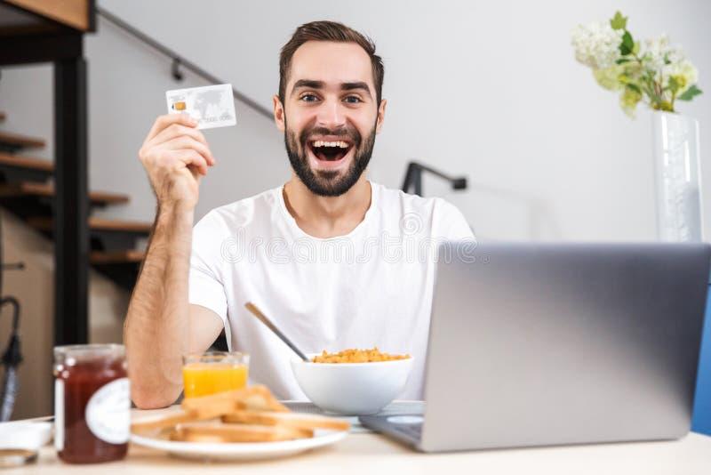 Jeune homme heureux prenant le petit déjeuner à la cuisine photographie stock