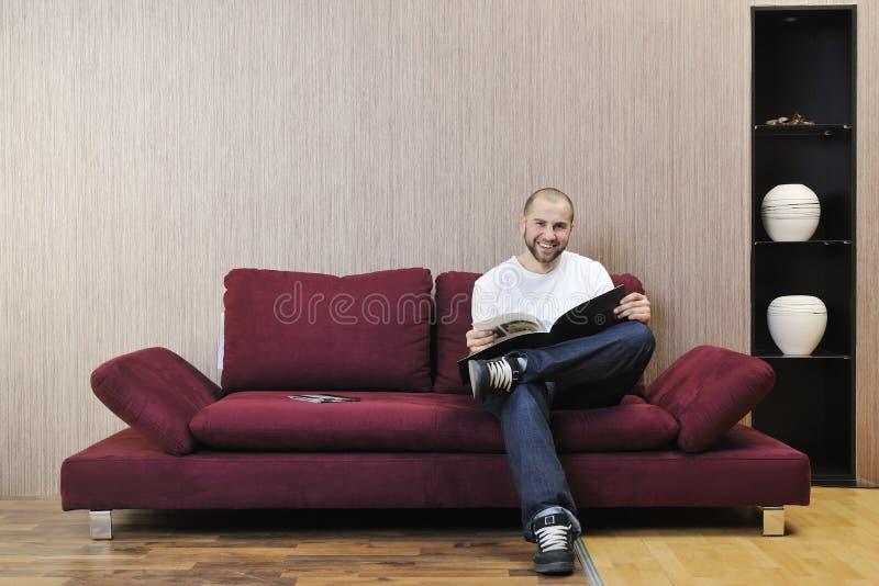 Jeune homme heureux realxing dans la salle de séjour moderne photographie stock