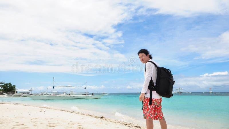 Jeune homme heureux regardant de retour l'appareil-photo sur tropical photographie stock