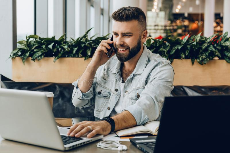 Jeune homme heureux s'asseyant dans le bureau à la table, travaillant à l'ordinateur, parlant au téléphone L'indépendant a des co photographie stock libre de droits
