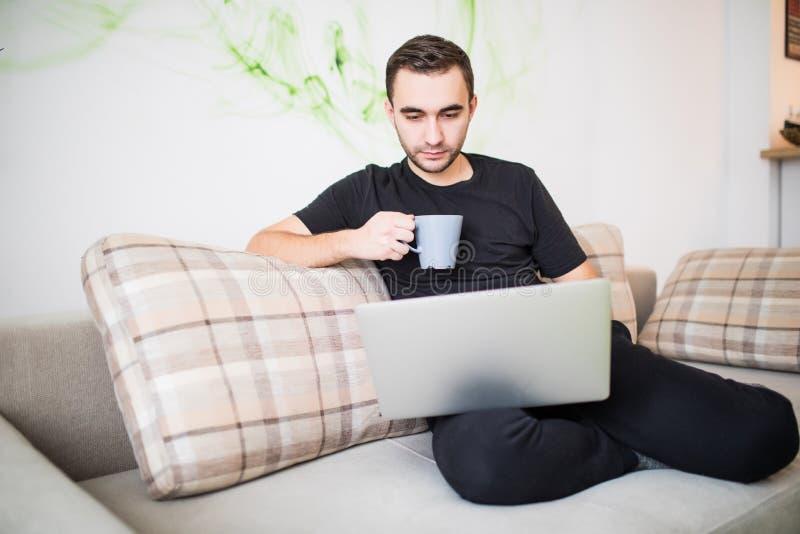 Jeune homme heureux s'asseyant dans le sofa et à l'aide de l'ordinateur portable photos stock