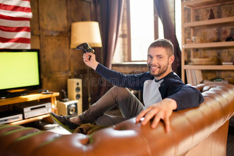 Jeune homme heureux s'asseyant sur le divan tenant le controler de jeu photographie stock
