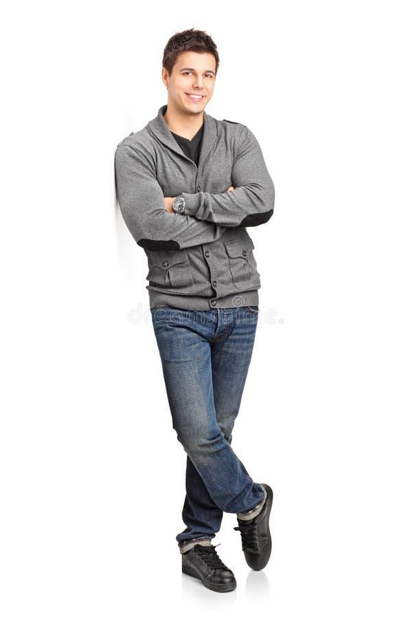 Jeune homme heureux se penchant contre le mur photographie stock libre de droits