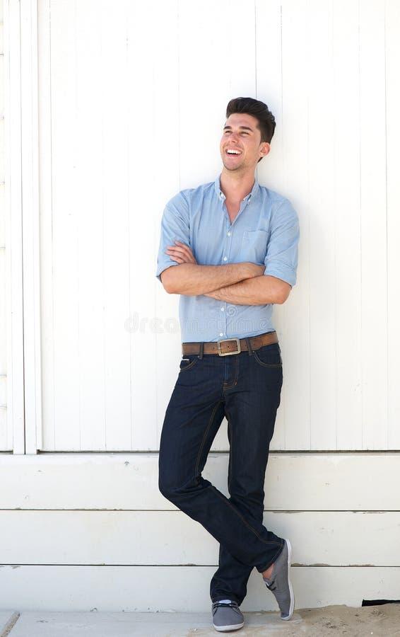 Jeune homme heureux se tenant sur le fond blanc photographie stock