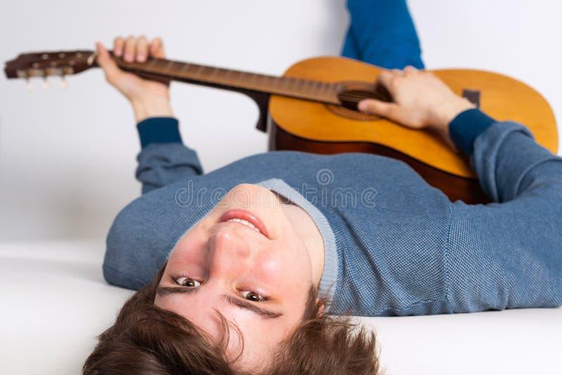 Jeune homme heureux se trouvant de retour sur le sofa avec la guitare photographie stock
