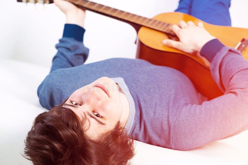 Jeune homme heureux se trouvant de retour sur le sofa avec la guitare image stock